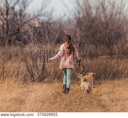 Back view of cheerful girl running with active dog in nature