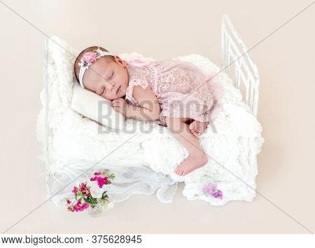 Sleeping newborn baby girl in a pink dress in a small crib