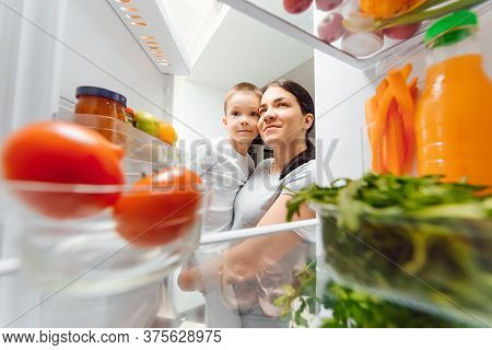 Mother With Her Baby Opening Refrigerator At Kitchen