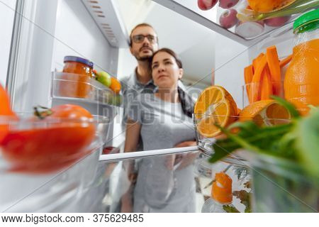 Happy Couple Near Open Fridge With Vegetables And Fruits. Healthy Nutrition Concept.