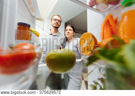 Portrait Of A Young And Happy Couple Standing With Fresh Vegetables Near The Refrigerator Full Of He