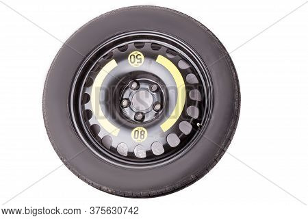 Full Size Black Car Spare Tire With Yellow Marking And Signs On A White Background In A Photo Studio
