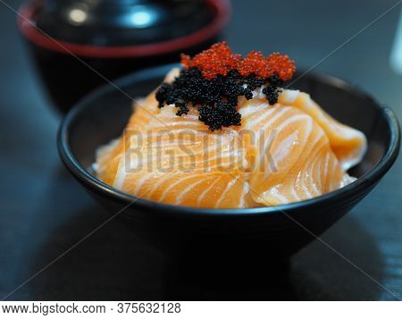 Sake Salmon Rice Japanese Style Chirashi Scattered Topping With Tobiko Flying Fish Roe In Black Bowl