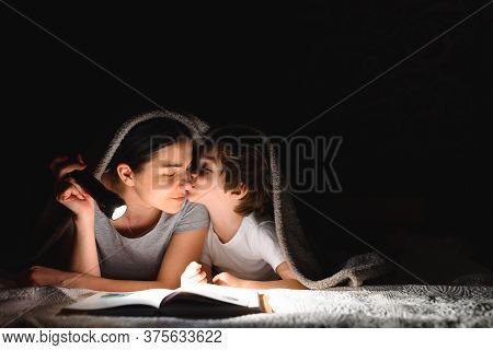 Family Mom And Little Son Reading A Book With A Flashlight Under The Blanket.