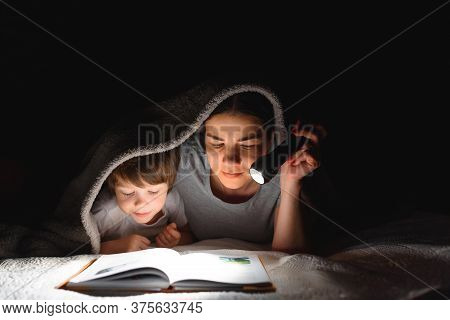 Happy Family. Time For Stories. Delighted Happy Cute Mother And Son Enjoying A Book Before Sleeping