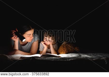 Happy Family Mother And Child Son Reading A Book With A Flashlight. Family Before Going To Bed Mothe