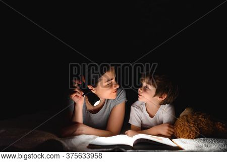 Family Bedtime. Mom And Children Son Are Reading A Book On Bed. Pretty Young Mother And Lovely Boy H