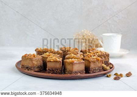 Raw Vegan Dessert. Chocolate Bars With Nuts And Dates On A White Background With A Cup Of Tea. Healt