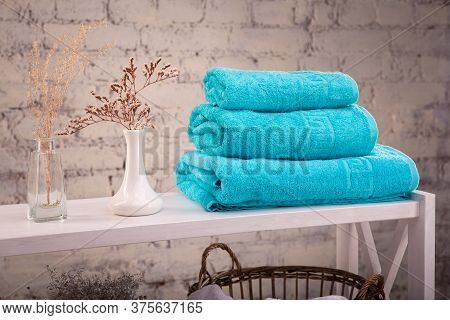 Rack With A Stack Of Three Color Turquoise Towels And Baskets With Clean White Towels And Toilet Dec