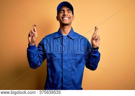 Young african american mechanic man wearing blue uniform and cap over yellow background gesturing finger crossed smiling with hope and eyes closed. Luck and superstitious concept.