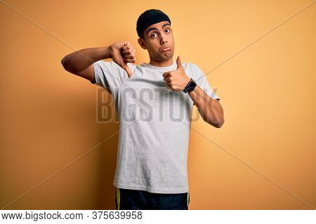 Handsome african american sportsman doing sport wearing sportswear over yellow background Doing thumbs up and down, disagreement and agreement expression. Crazy conflict