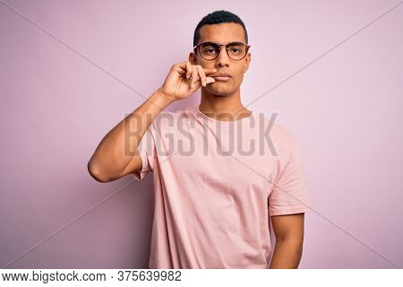 Handsome african american man wearing casual t-shirt and glasses over pink background mouth and lips shut as zip with fingers. Secret and silent, taboo talking