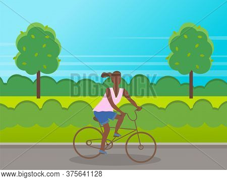 Young Sportive Girl Wearing T-shirt And Shorts With Ponytail Riding At Bicycle In Park. Black Skin G