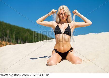 Full body portrait of a young beautiful blonde girl in black bikini