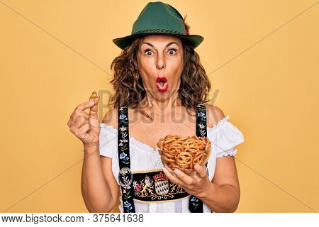 Middle age woman wearing traditional octoberfest dress holding bowl with baked pretzels scared in shock with a surprise face, afraid and excited with fear expression