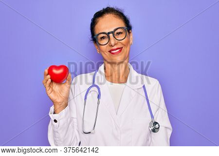 Middle age senior cardiologist doctor woman holding red heart over purple background with a happy face standing and smiling with a confident smile showing teeth
