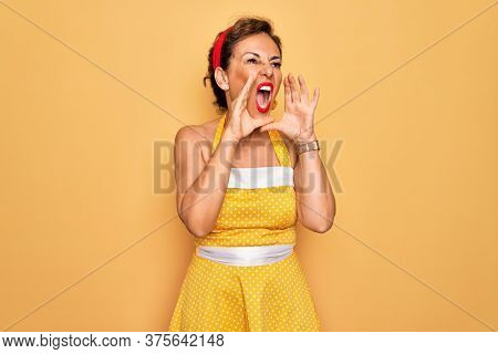 Middle age senior pin up woman wearing 50s style retro dress over yellow background Shouting angry out loud with hands over mouth