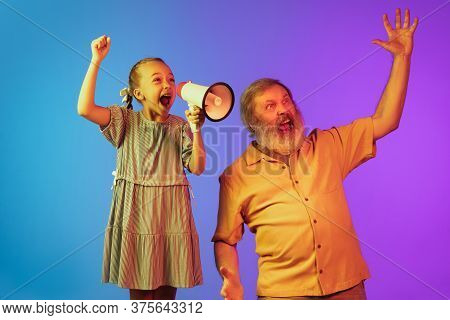Shouting With Megaphone. Senior Man Spending Happy Time With Granddaughter In Neon. Joyful Elderly L