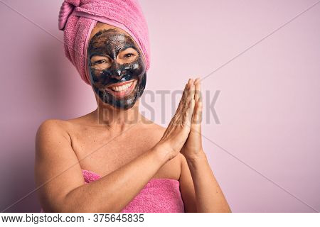 Middle age brunette woman wearing beauty black face mask over isolated pink background clapping and applauding happy and joyful, smiling proud hands together