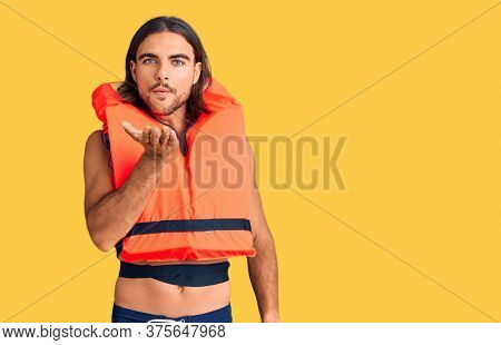 Young handsome man wearing nautical lifejacket looking at the camera blowing a kiss with hand on air being lovely and sexy. love expression.
