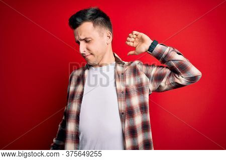Young handsome caucasian man wearing casual modern shirt over red isolated background stretching back, tired and relaxed, sleepy and yawning for early morning