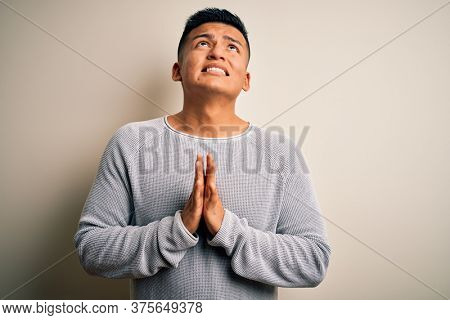 Young handsome latin man wearing casual sweater standing over isolated white background begging and praying with hands together with hope expression on face very emotional and worried. Begging.
