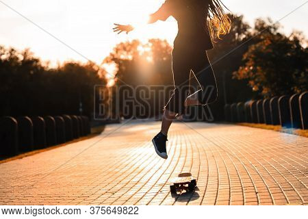 Silhouette Of A Girl In Gym Shoes Jumping On A Skateboard In The Setting Sun In The Park