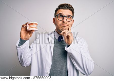 Young dentist man with blue eyes holding orthodontic dental prosthesis over isolated background serious face thinking about question, very confused idea