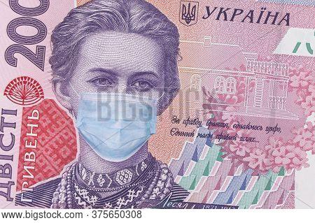 Covid-19 Coronavirus In Ukraine. 200 Hryvnia Banknote With Lesya Ukrainka In A Medical Mask. Global