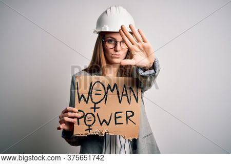 Young redhead architect asking for women rights holding banner with woman power message with open hand doing stop sign with serious and confident expression, defense gesture