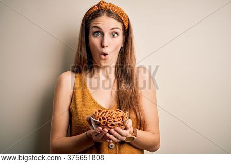 Young beautiful redhead woman holding bowl with german baked pretzels scared in shock with a surprise face, afraid and excited with fear expression