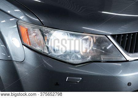 Novosibirsk/ Russia - April 22 2020: Mitsubishi Outlander Xl, Gray Car Headlights. Exterior Detail.