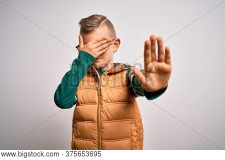 Young little caucasian kid with blue eyes wearing winter coat and smart glasses covering eyes with hands and doing stop gesture with sad and fear expression. Embarrassed and negative concept.