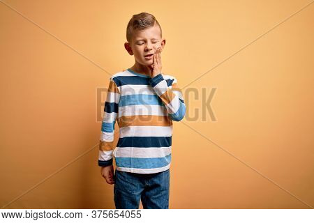 Young little caucasian kid with blue eyes wearing colorful striped shirt over yellow background touching mouth with hand with painful expression because of toothache or dental illness on teeth.