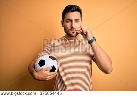 Handsome player man with beard playing soccer holding footballl ball over yellow background mouth and lips shut as zip with fingers. Secret and silent, taboo talking