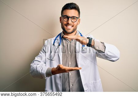 Young doctor man wearing glasses, medical white robe and stethoscope over isolated background gesturing with hands showing big and large size sign, measure symbol. Smiling looking at the camera.
