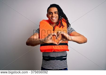 Young african american afro man with dreadlocks wearing orange lifejacket smiling in love showing heart symbol and shape with hands. Romantic concept.