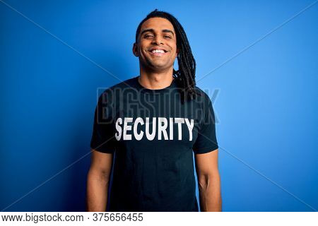 Young african american afro safeguard man with dreadlocks wearing security uniform with a happy face standing and smiling with a confident smile showing teeth