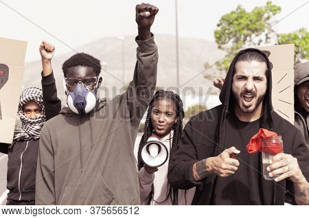 Young Black Man With Gas Mask Marching Crowd Of People With Raised Fists On Public Demonstrations. B
