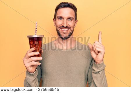 Young handsome man drinking cola refreshment beverage over isolated yellow background smiling happy pointing with hand and finger to the side