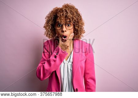 Young african american businesswoman wearing glasses standing over pink background Looking fascinated with disbelief, surprise and amazed expression with hands on chin