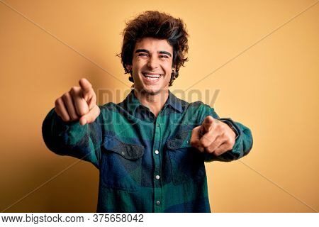Young handsome man wearing casual shirt standing over isolated yellow background pointing to you and the camera with fingers, smiling positive and cheerful