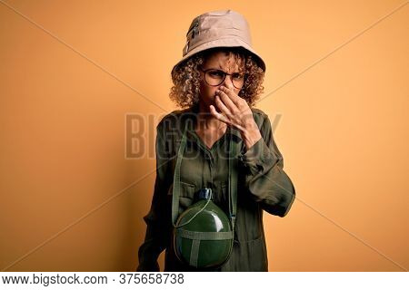 Young african american tourist woman on vacation wearing explorer hat and water canteen smelling something stinky and disgusting, intolerable smell, holding breath with fingers on nose. Bad smell