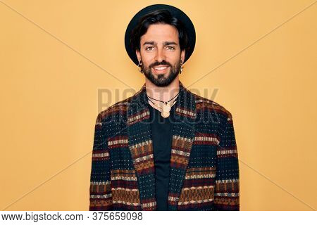 Young handsome hispanic bohemian man wearing hippie style and boho hat with a happy and cool smile on face. Lucky person.