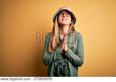 Beautiful blonde explorer woman with blue eyes wearing hat and glasses using binoculars begging and praying with hands together with hope expression on face very emotional and worried. Begging.