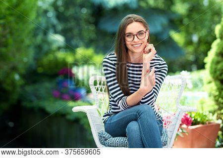 Beautiful Young Woman Sitting At Home In The Garden And Smiling