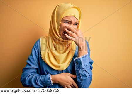Young beautiful woman with curly hair wearing arab traditional hijab over yellow background smelling something stinky and disgusting, intolerable smell, holding breath with fingers on nose. Bad smell