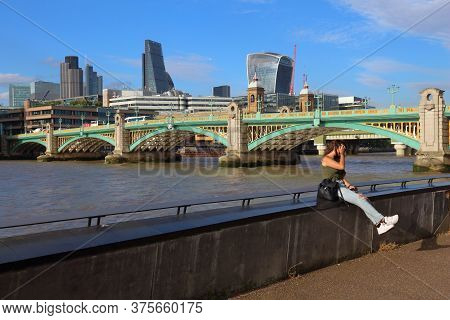 London, Uk - July 8, 2016: Person Sits At London Embankment In The Uk. London Is The Most Populous C
