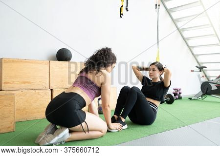 Young Woman Motivating Friend In Doing Sit-ups In Cross-training Gym