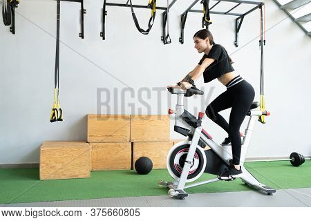 Confident Fit Young Woman Cycling On Exercise Bike At Cross-training Gym